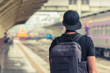 Man with backpack waiting for a train in a train station. Travel backpacker concept
