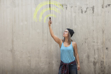 Woman holding up phone looking for signal with wifi sign drawn in yellow chalk on concrete wall