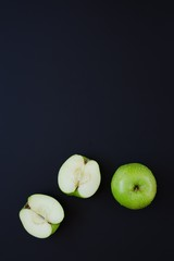 Green apple and two halves of apple on black background