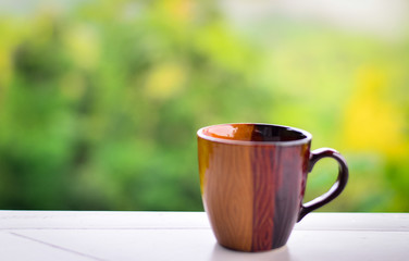 Brown coffee cup on green blur background.