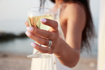Wedding ceremony objects, signs, symbols, attributes and accessories. Bride hand in ring with glass of champagne to celebrate love and happiness, piece and cheers. Blurred background, romantic mood