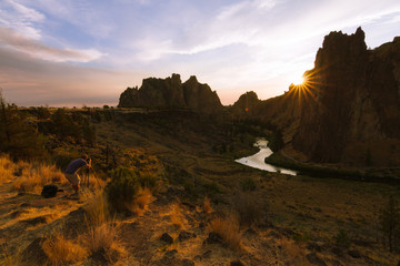 Man taking pictures of Colorful Sunset Over Smith Rock State Park and Crooked river in Central Oregon