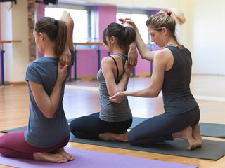 Women practicing yoga and stretching arms