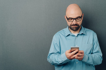 Portrait of a man sending messages on mobile phone