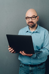 Bald man in glasses with laptop computer