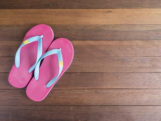 Pink flip flop on wooden floor 3