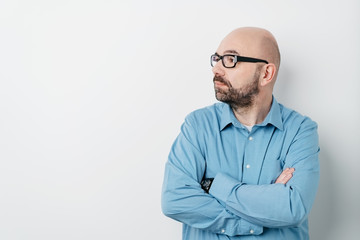 Thoughtful bald man looking to side