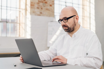 Unhappy businessman working on a laptop