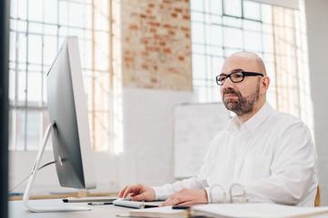 Businessman working on a large desktop monitor