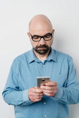 Portrait of serious man sending messages on mobile