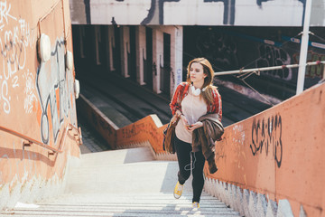 Young beautiful woman walking upstairs in the city holding smart phone - everyday life, technology, city living concept