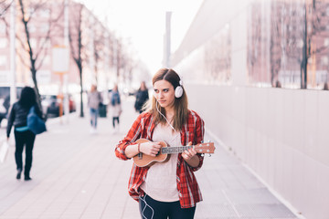 Young woman in the city playing ukulele - busker, musician, composer concept
