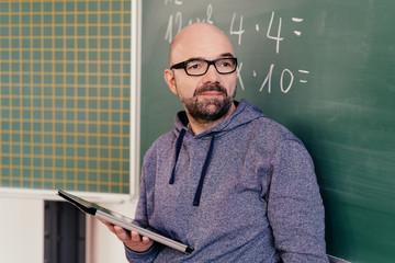 Maths teacher standing in front of a blackboard