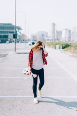 Young beautiful woman walking in the city holding ukulele - busker, city living, music concept