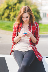 Young woman in the city using smart phone hand hold - technology, social network, phubbing concept