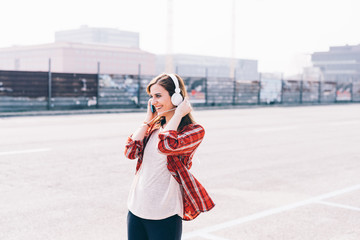 Young woman outdoor in the city listening music with headphones and smartphone hand hold - music, relaxing, technology concept