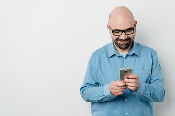 Man smiling while sending messages on mobile