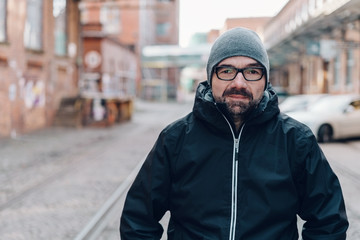 Modern urban man in anorak and knitted cap