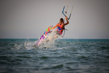 Kite surfing girl in sexy swimsuit with kite in sky on kiteboard in the blue sea riding waves saying hi. Recreational activity, water sports, action, hobby and fun in summer time. Kiteboarding sunset