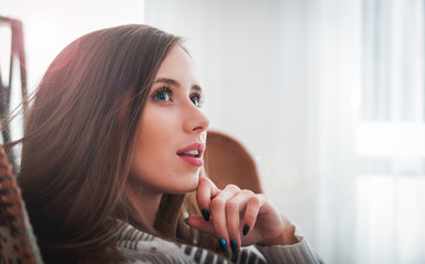 Woman at home sitting on chair and thinking about something