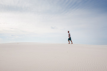 Lost in the desert is walking along the dune