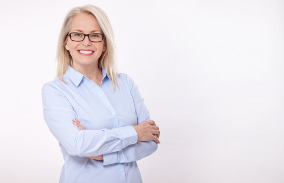 Middle aged business woman with eyeglasses in blue shirt isolated on white background