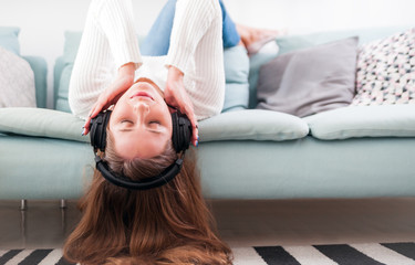 Woman with headphones on sofa at home listening music