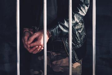 Handcuffed man behind prison bars