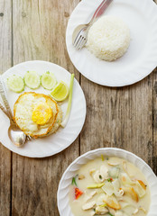 authentic Thai dinner background: Tom kha gai spicy soup, plain rice and pad kra pao with fried egg on top on wooden table at local cafe. Asian food concept. Text space