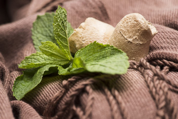 Mint leaves and ginger root lying on brown cloth.