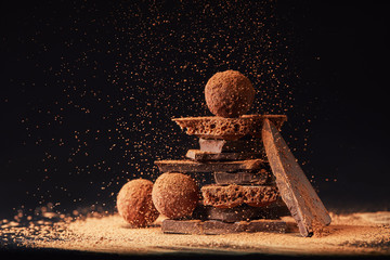 close up view of arrangement of truffles and chocolate bars with cocoa powder on black