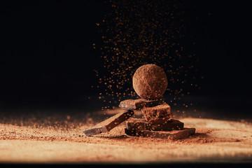 Fototapeta close up view of truffle on chocolate bars with cocoa powder on black obraz