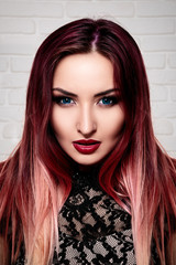 Elegant girl or woman with beautiful make-up stands on white background wall, close-up portrait of fashion. With pink hair and blue eyes