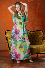 Attractive beautiful slender blonde girl-model posing in a bright long silk dress and standing in full height on high heels. Happy young woman smiling.