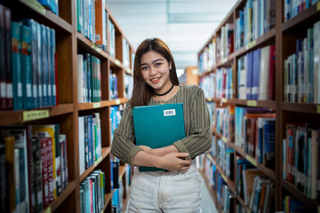 Asia girl holding a book in public library.