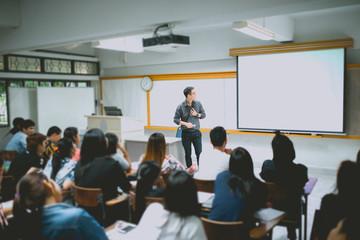 Obraz Teacher teaching studen in classroom at university. - fototapety do salonu