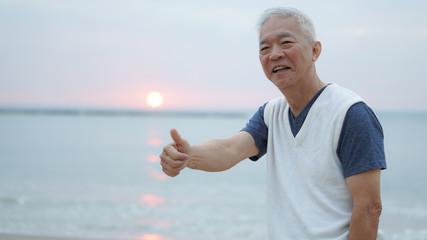 Asian senior man thumbs up at sunrise financial worry free