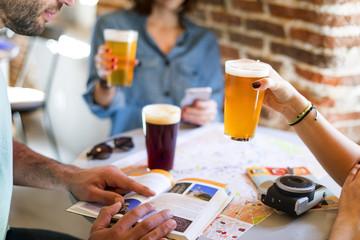 Turistas beben cerveza y buscan un lugar en una guía turística