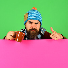 Hipster with tricky face holds tea or coffee cup