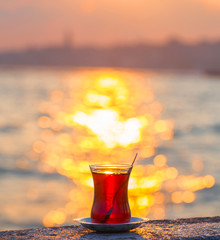A cup of Turkish tea against the backdrop of the sunset and the Bosporus Strait