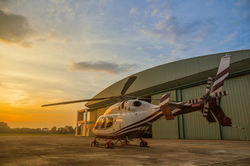 Wall Murals Helicopter silhouette of helicopter in the parking lot or runway with sunrise background,twilight helicopter on the helipad