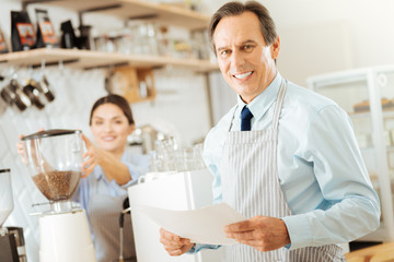 Simply work day. Handsome joyful satisfied man standing near the coffee machine smiling and holding the document.