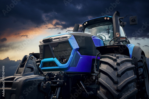 Fototapete Powerful tractor against a stormy sky