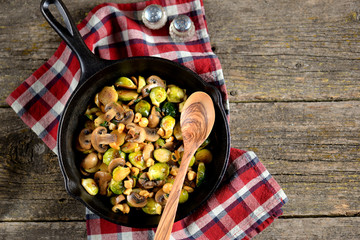 Fried Brussels sprouts with mushrooms and nuts on a cast-iron frying pan on a wooden background.