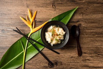 Shrimp wonton with braised pork in soup on wooden table - Asian food style  / Select focus image