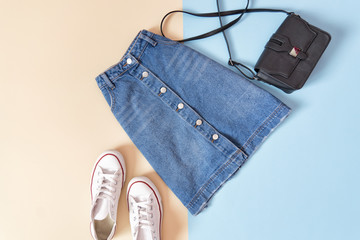Fashionable concept. Female urban style. Denim skirt, handbag and white sneakers on a blue background, beige