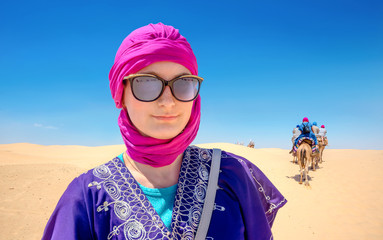 Beautiful woman in arabic traditional clothing against Sahara desert background. Tunisia, North Africa