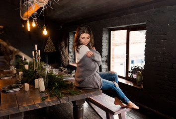 Sensuality gorgeous girl wearing in gray and white knit sweater sitting on table and posing at camera. Pretty and beautiful young female at stylish kitchen with loft interior. Christmas. Cozy home.