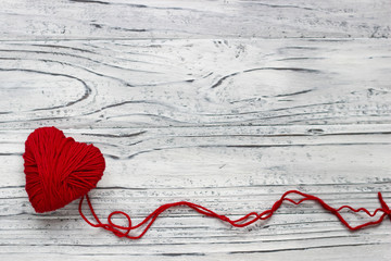 Heart in the form of a string of threads from which a red sweater knits. Valentines day concept.