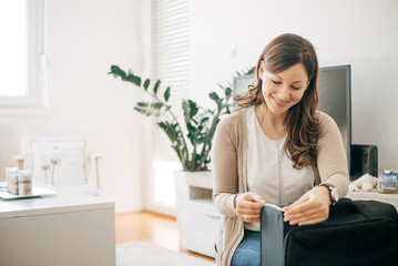 Woman at home measuring luggage before going on holiday vacation.